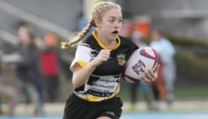 Young girl playing rugby
